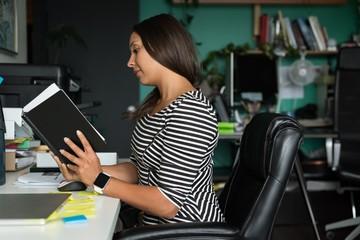 Female executive reading diary at desk