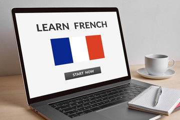 Learn French concept on modern laptop computer screen on wooden table. All screen content is designed by me.