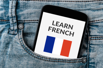 Learn French concept on smartphone screen in jeans pocket. All screen content is designed by me. Flat lay