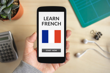 Hand holding smart phone with learn French concept on screen. All screen content is designed by me. Flat lay