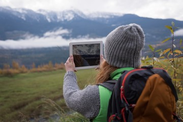 Woman taking picture of mountain with digital tablet