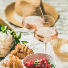 French style romantic summer picnic setting. Flat-lay of glasses of rose wine with ice, fresh strawberries, croissants, brie cheese, straw hat, peony flowers, square crop. Outdoor gathering concept