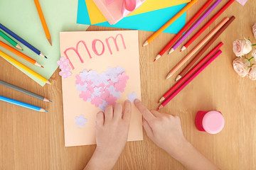 Little girl preparing greeting card for her mommy on Mother's Day at table