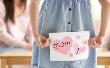 Little girl hiding greeting card for mommy behind her back on Mother's Day