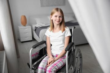 Teenage girl in wheelchair indoors