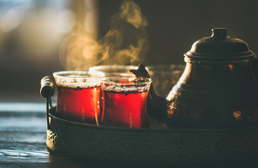 Traditional hot steaming Turkish tea in tulip glasses with copper pot in vintage tray