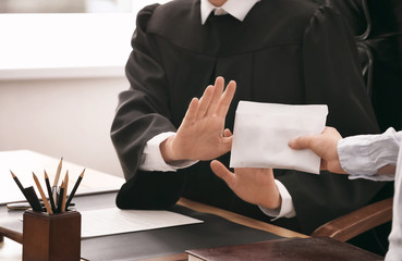 Judge refusing to take bribe from woman, closeup