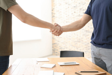 Two young men shaking hands over table. Unity concept