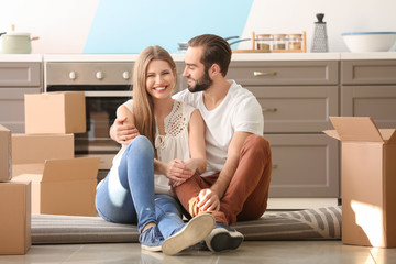 Young couple with moving boxes on floor in kitchen at new home
