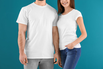 Young man and woman in stylish white t-shirts on color background. Mockup for design