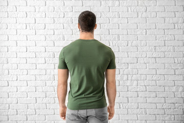 Young man in stylish t-shirt near white brick wall. Mockup for design