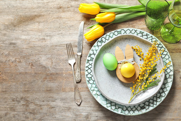 Beautiful festive Easter table setting with painted eggs and mimosa on wooden background