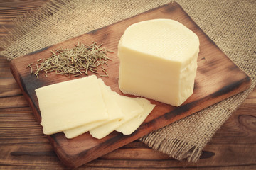 Suluguni cheese sliced on wooden plate with dried rosemary condiment