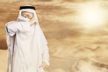 Scheich hält sich schützend das keffiyeh vor dem Mund wegen Wüstensturm