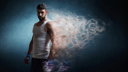Muscular male boxer standing over dark background particles effect.