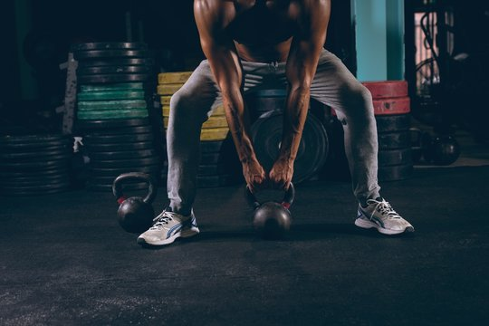 Low section of muscular man exercising with kettlebell