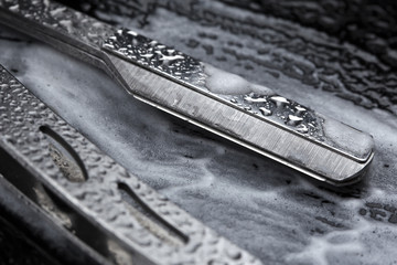 Nahaufnahme einer Shavette aus Edelstahl auf einem Untergrund mit Carbon Struktur