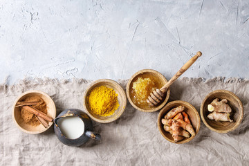 Ingredients for turmeric latte. Ground turmeric, curcuma root, cinnamon, ginger, honeycombs in wooden bowls, jug of milk over grey texture background with textile linen. Top view, copy space