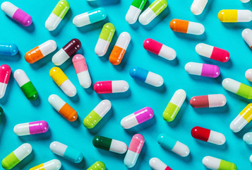 different color pills on blue background. Drugs and medicines