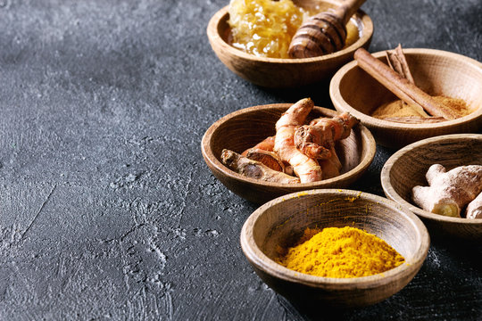 Ingredients for turmeric latte. Ground turmeric, curcuma root, cinnamon, ginger, honeycombs in wooden bowls over black texture background. Close up, copy space