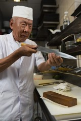 Senior chef holding knife in the kitchen