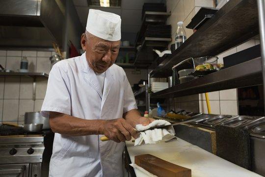 Senior chef holding knife in kitchen