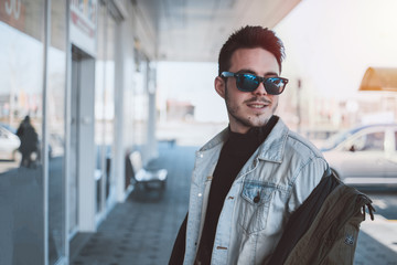 Young attractive male model looking in distance and smiling. Fashion, texas, sunglasses wearing.