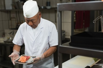 Senior chef holding plate of sushi in kitchen