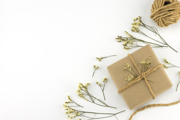Brown gift boxes and rope with yellow limonium caspia flowers on white wood background with copy space