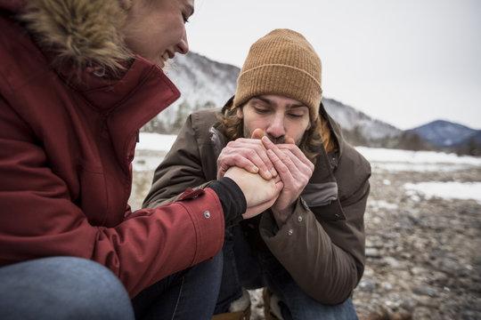 Boyfriend warming girlfriend's hands