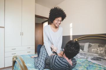 young multiethnic people bedroom tickling