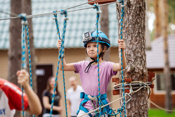 baby girl with climbing gear  in an adventure park are engaged in rock climbing or pass obstacles on the rope road.