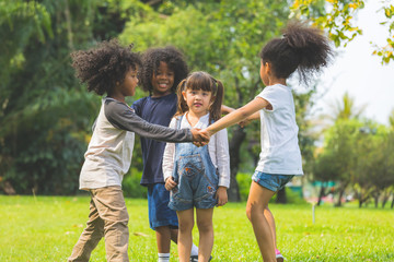 Group of kids have fun playing game holding hands in circle in the park