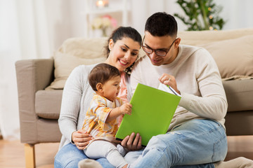 happy family with baby reading book at home