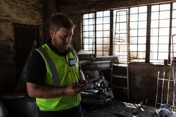 Worker using digital tablet in the junkyard