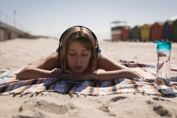 Teenage girl listening music on headphones while relaxing on the beach