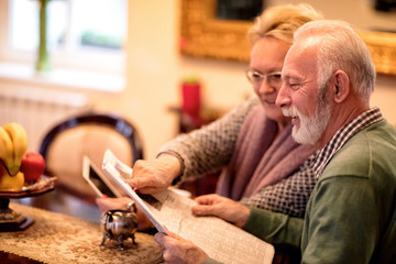 Senior couple having fun while reading newspaper and using tablet