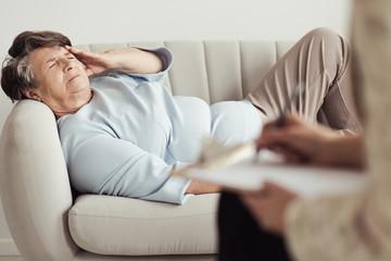 Sad elderly woman with headache