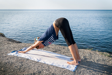 Young girl is standing in yoga dog pose on a stony sea coast in summer morning.