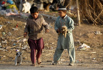 Children play with puppies at an Afghan refugee camp in Islamabad