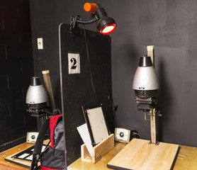 Two old black and white enlargers in a dark room