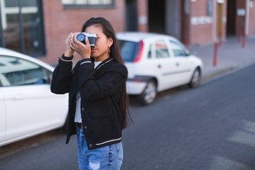 Teenage girl taking photo with camera