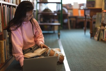 Young woman sitting in library with laptop and book
