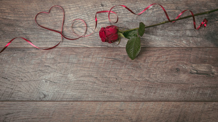 The red ribbon is lined in the shape heart on a dark wooden table. Valentines day background, rustic style. Valentines day table place setting with red rose and ribbon. Flat lay, top view.