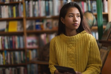 Teenage girl using digital tablet in library