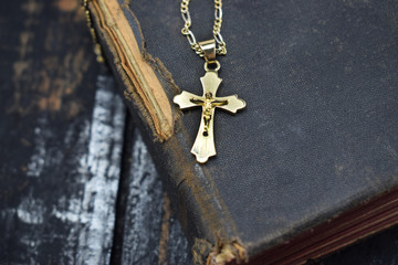 a golden cross lies and an ancient holy bible on the table