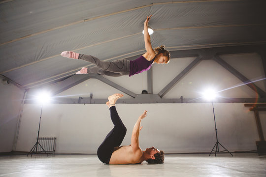 The theme of Acroyoga and Yoga Poses. Acroyogis practicing. with studio Backlight. the Base man tosses the Pops woman Flyer in flight up. Position Acrobatic flying