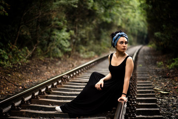 An attractive lonely young woman  with long black hair, wearing black long dress and turban, is sitting on the railway tracks, summer nature outdoor, tone color