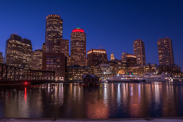 Etiqueta Engomada - Night view of the city, skyscrapers in the lights. Skyscrapers on the shore of the bay, lights reflected in the water, boats at the pier. Boston. USA.