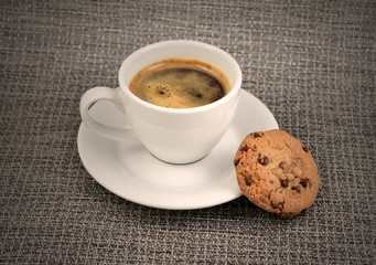 Chocolate cookie with coffee stock images. White cup of coffee with snack. Cup of coffee with cookie. Espresso with sweetness